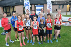 Wendy Percey of Lesley Shand Funeral Directors, centre, and Garry Dickerson of Seyward Window Ltd, blue top, and Cllr Paul Harrison representing the Corfe Mullen Parish Council with the winners of the Corfe Mullen 5K and children's one mile run.